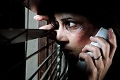 Fearful battered woman peeking through the blinds to see if her husband is home while calling for he