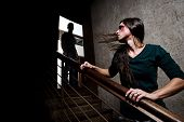 Concept of domestic abuse. Battered woman escaping from man silhouetted at the top of the stairs, in