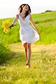 image of summer fun  - Candid skipping carefree adorable woman in field with flowers at summer sunset - JPG
