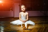 A Pretty Small Ballerina In White Dress Wearing Her Point Shoes Sitting On Woody Floor Posing On Cam poster