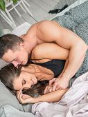 Image Of Cute Young Couple In Love Lying On Bed. Man Waking Up His Wife In Morning. poster