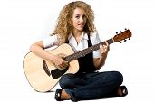 stock photo of young adult  - A pretty young woman playing acoustic guitar on white background - JPG