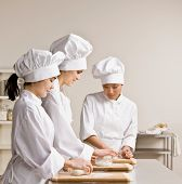 Chef co-workers in toques and chef?s whites kneading dough in commercial kitchen