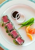Seared tuna with sesame seeds with green salad on white plate poster