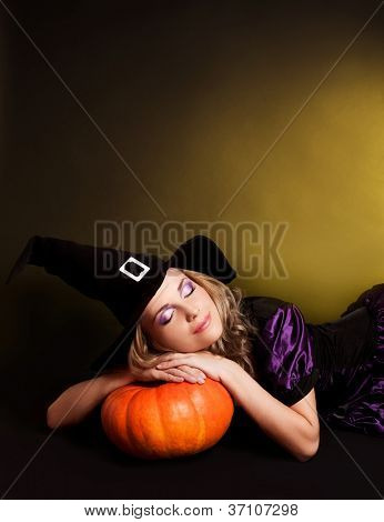 beautiful sleeping witch with a pumpkin, against yellow studio background, copy-space for your text on the top