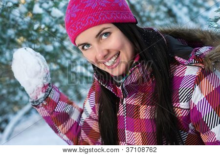 Beautiful young woman outdoor in winter playing snowballs
