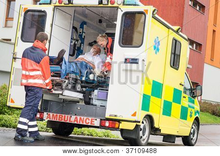 Paramedics putting patient man oxygen mask in ambulance car