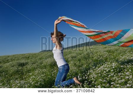 Young woman standing jumping and running  on a wheat field with blue sky in  background at summer day representing healthy life and agriculture concept