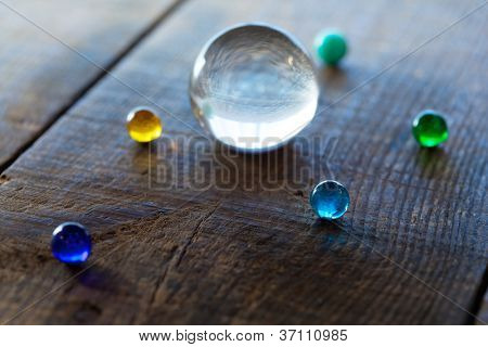 Big and small marble or glass spheres on a old desk, resembling a planetary  formation.