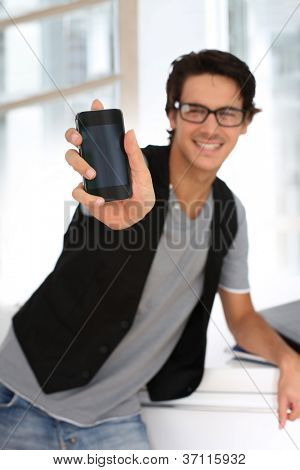 Student in building showing smartphone to camera