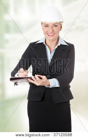 Happy mature engineer woman making notes.