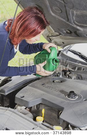 Cute woman is adding oil in the car