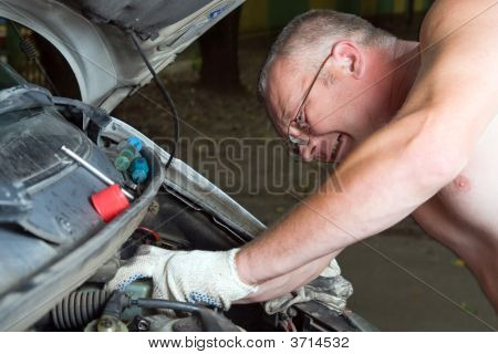 The Man Repairs Car