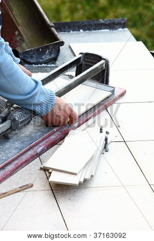 Man Cutting Tile By Cutter