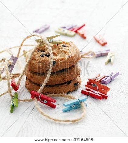 Close up chocolate cookies and cloth pegs on wooden table