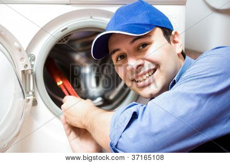 Portrait of a technician repairing a washing machine