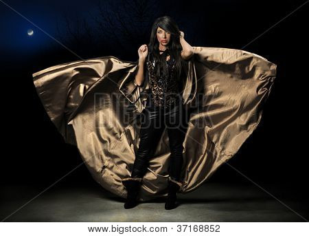 Female vampire with flying cloak over dark background