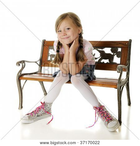 A pretty elementary girl sitting on a bench, delighted with her over-sized, high-top, sparkly sneakers.  On a white background.