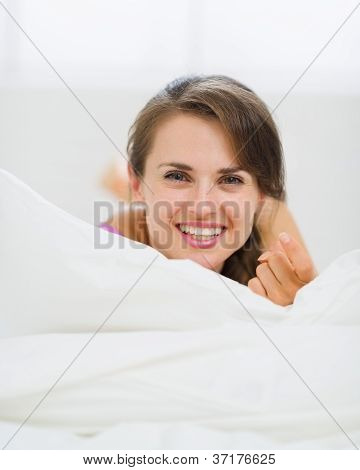 Happy Young Woman Laying On Bed And Beckoning With Finger