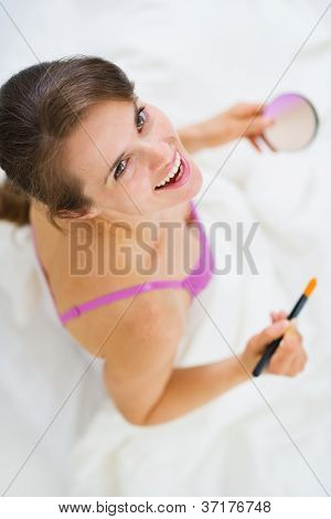 Smiling Young Woman Applying Makeup. Upper View