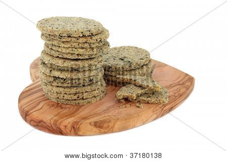 Laverbread savoury biscuits on an olive wood heart shaped board over white background. Welsh specialty.