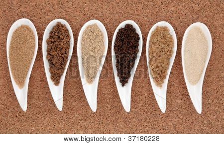 Selection of demerara, muscovado, granulated, molasses, crystal and light and brown, sugar in white porcelain dishes over cork background.