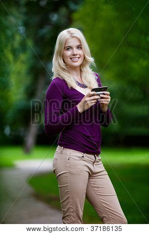 Mujer con celular en el parque.