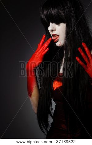 Young mysterious fashion vampire woman lick bloody fingers