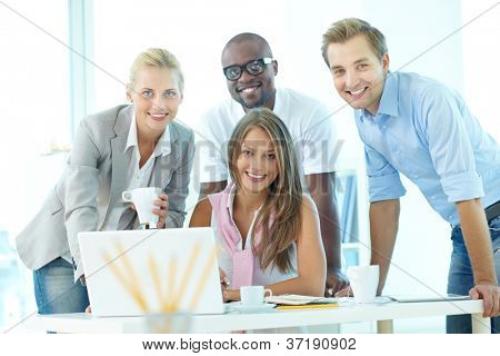 Group of friendly students or businesspeople gathered in front of laptop looking at camera