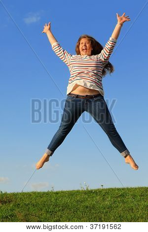 Young girl in jeans jumps and screams at green grass at background of blue sky.