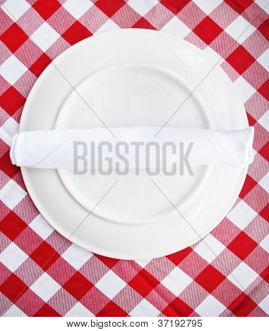 Red and white checkered table cloth with plate