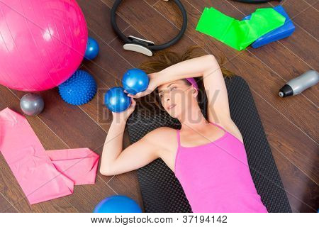 Aerobics instructor woman tired resting lying on mat with pilates balls and bands