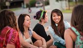 stock photo of bff  - Diverse group of happy teenage girls sitting and talking - JPG