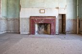 stock photo of wainscoting  - A previously formal room with fireplace and blank picture over the mantal in an old long abandoned large house - JPG