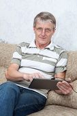 Senior Adult Caucasian Man Working With A New Tablet Computer, Sitting On Sofa In Domestic Room poster