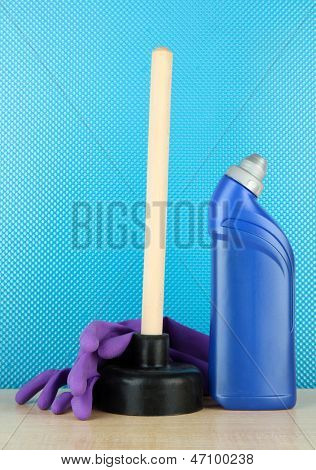 Toilet plunger, gloves and cleaner bottle on blue background