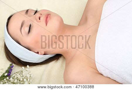 Beautiful young woman lying in spa salon with flowers close up