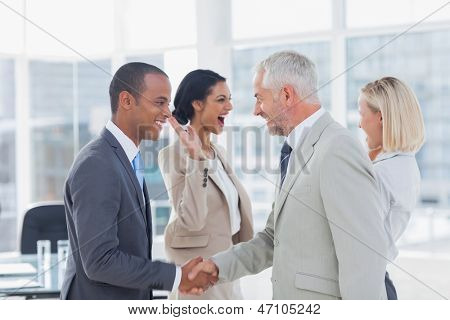 Succesful business team shaking hands and high fiving in the office