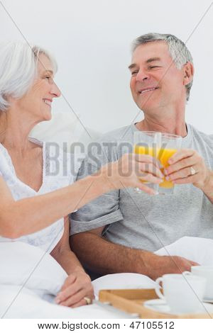 Couple clinking their orange juice glasses while having breakfast in bed