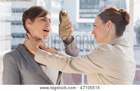 Businesswoman defending herself from her colleague strangling her in a bright office