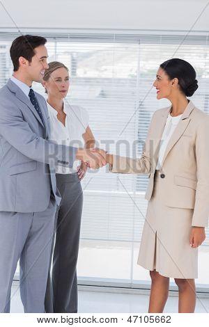 Händeschütteln im hellen Büro während Kollege beobachtete sie Geschäftsleute