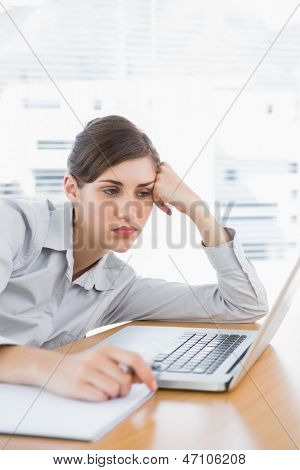 Fed up businesswoman at her desk looking at laptop