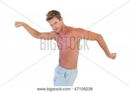 Shirtless man gesturing and showing his muscles on white background