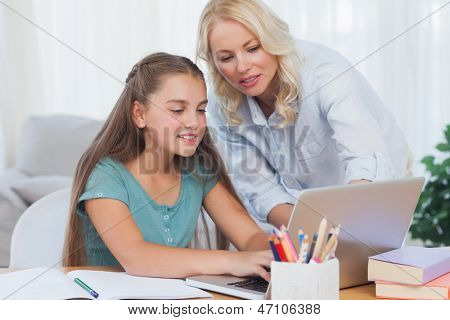 Mother helping her daughter to do homework with a laptop