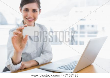 Young businesswoman showing blank business card at her desk in office