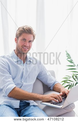 Attractive man sitting on the couch and using his laptop in the living room