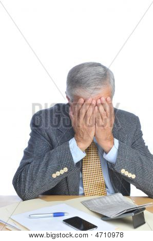 Middle Aged Businessman Seated At His Desk With Face In Hands