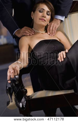 Hispanic woman in evening gown having shoulders massaged