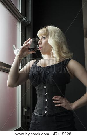 Beautiful Young Woman With Blond Hair Drinking A Glass Of Wine