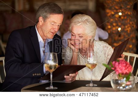 Senior Couple Choosing From Menu In Restaurant